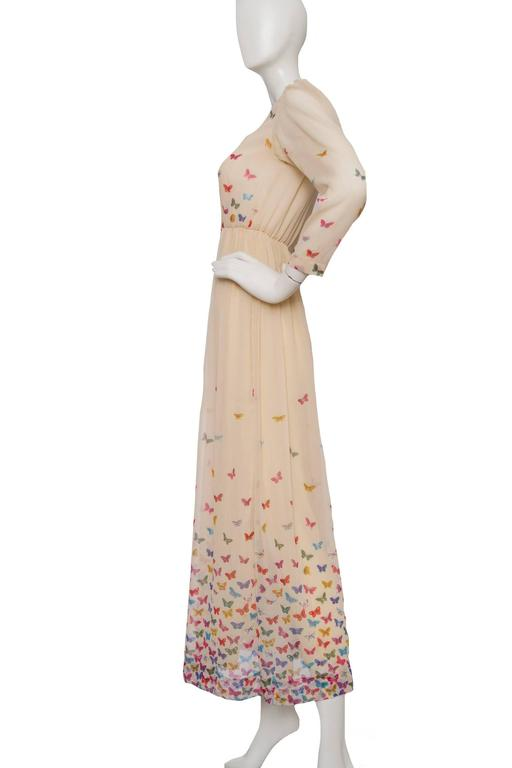 A delicate 1970s Hanae Mori beige silk dress with a nipped in elasticated waist, a sheer blouse and a multi-layered & pleated floor-length skirt. The dress has long tapered sleeves, a silk satin trim along a scoop neckline and a buttoned down