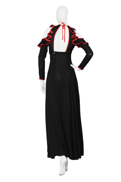 An absolutely stunning 1970s black Ossie Clark ankle-length moss crepe dress with long tapered sleeves and cut-out shoulders. The dress has a fitted waistline and a key-hole cut-out in the front, with contrasting red piping. The red silk is repeated