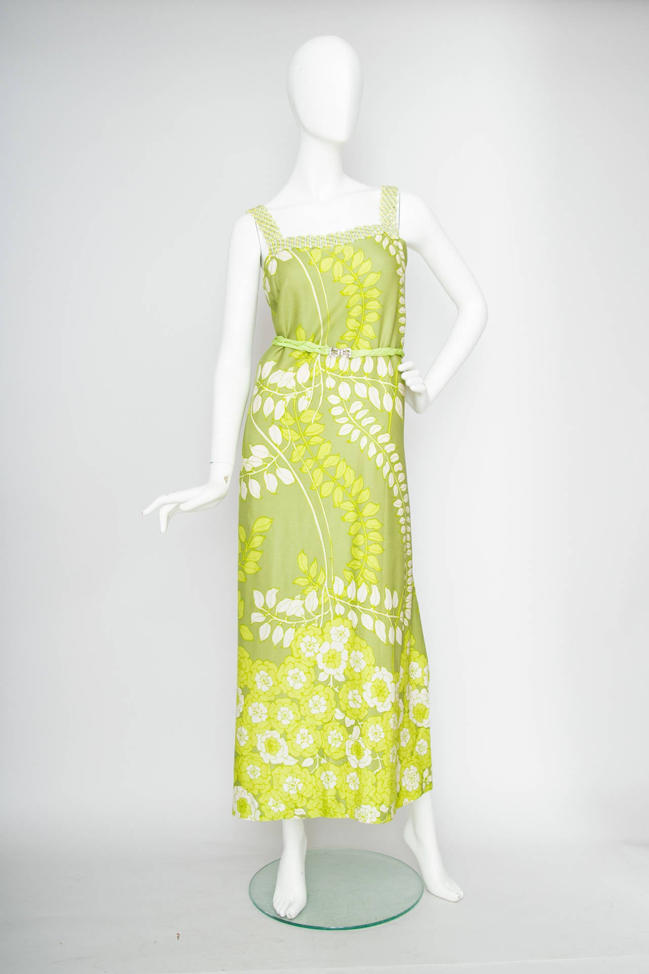 A gorgeous 1960s green handmade silk evening dress with an overall leaf and flower print, that gracefully cascades from leaf into a flowerbed.  The dress features a beaded top piece and has a braided belt with a silver and rhinestone studded