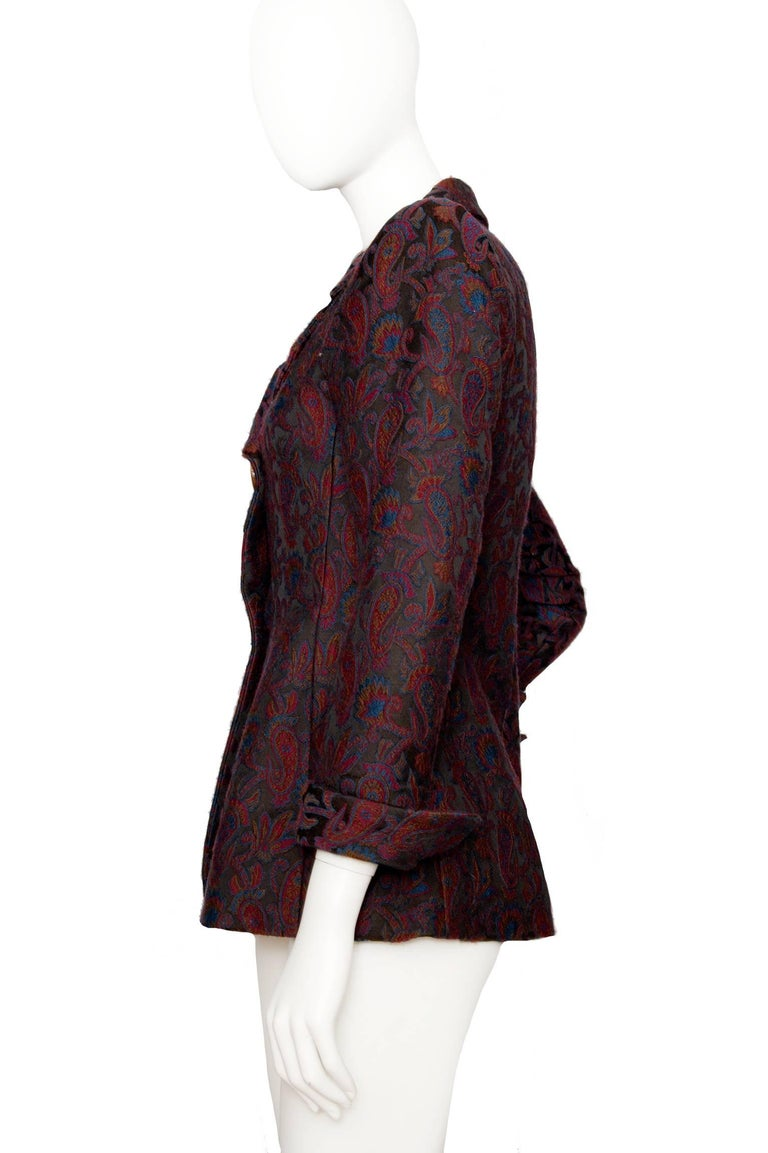 A 1980s Yves Saint Laurent Rive Gauche tapestry blazer with an asymmetrical front buttoned closure and long tapered sleeves with turn up cuff. The color of the tapestry pattern consists of a dark burgundy and blue colors intertwined to form a