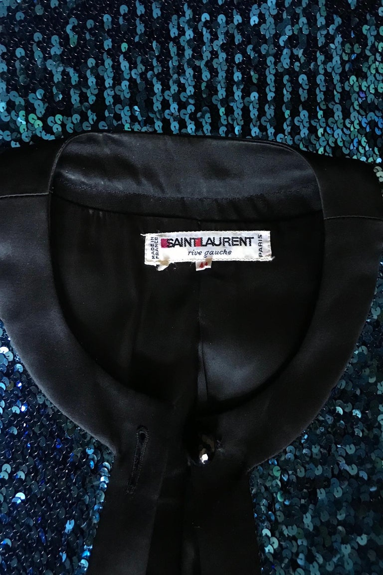 An absolutely fabulous 1980s Yves Saint Laurent Rive Gauche blue sequined skirt suit consisting of a fitted jacket and pencil skirt.   The jacket has long tapered sleeves, shoulder-pads, a front buttoned closure and black trim around the cuffs,