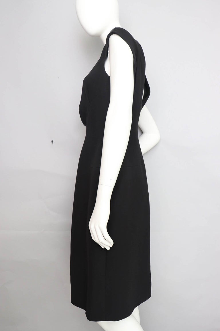 A great 1990s Chanel little black silk dress with cap sleeves and ruching in the center front. The gorgeous simple dress has a fitted waist and paneling that beautifully mirrors the curves of the hip. The dress is fully lined in black silk and has a