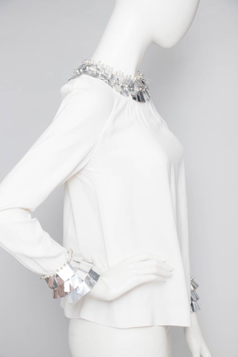 A rare 1970s Chloé by Karl Lagerfeld white silk blouse with metallic plate trimming around the collar and cuff. The trim is further embellished with whte beads. The cuff has a triple button closure and a back zipper and hook & eye closure.   The