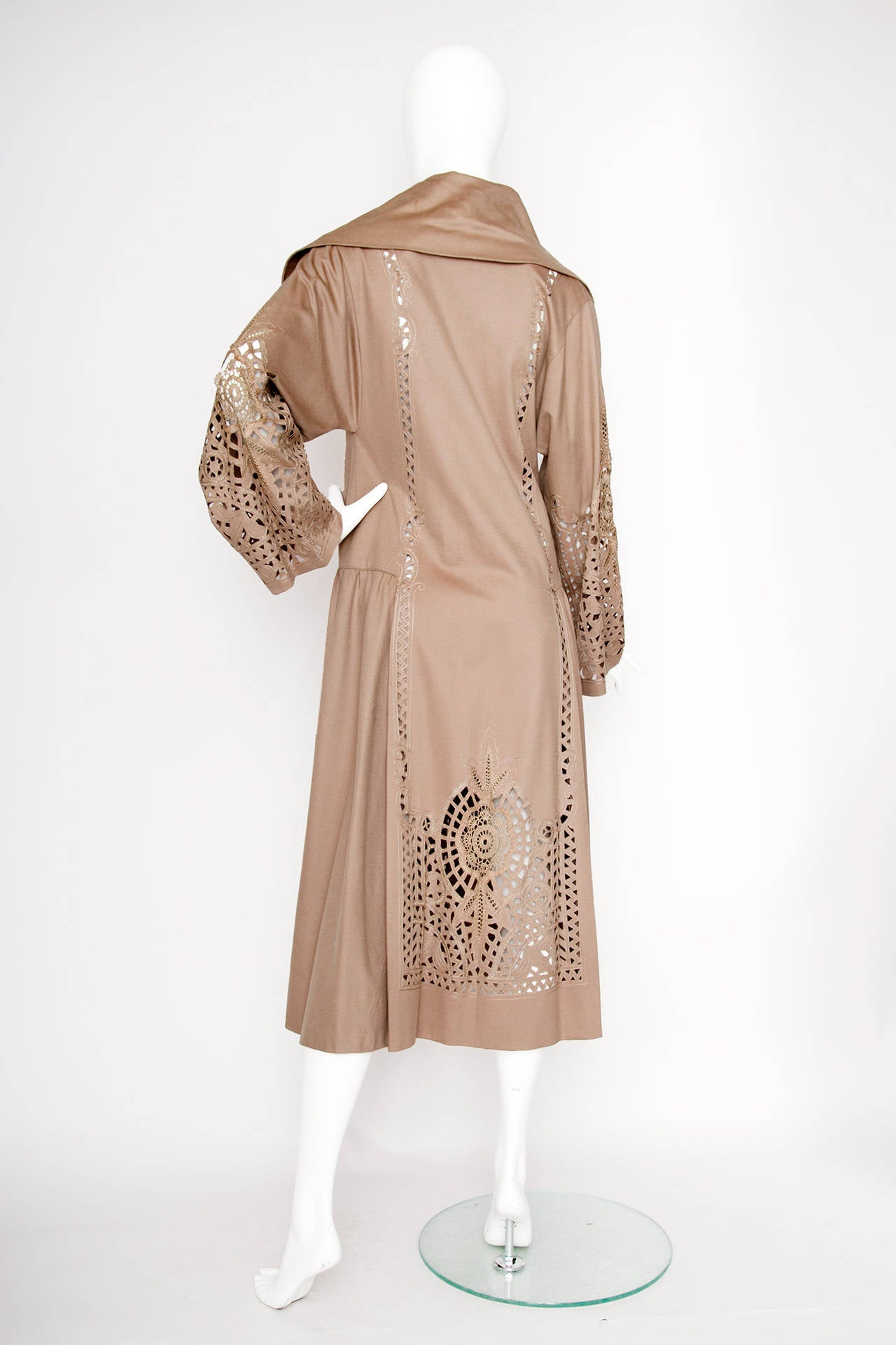 A beautiful 1920s floor length cloak like coat with long sleeves, a wide broad collar, two large centered buttons and an all over detailed stitching and cut work pattern on the sleeves and down the front and back.