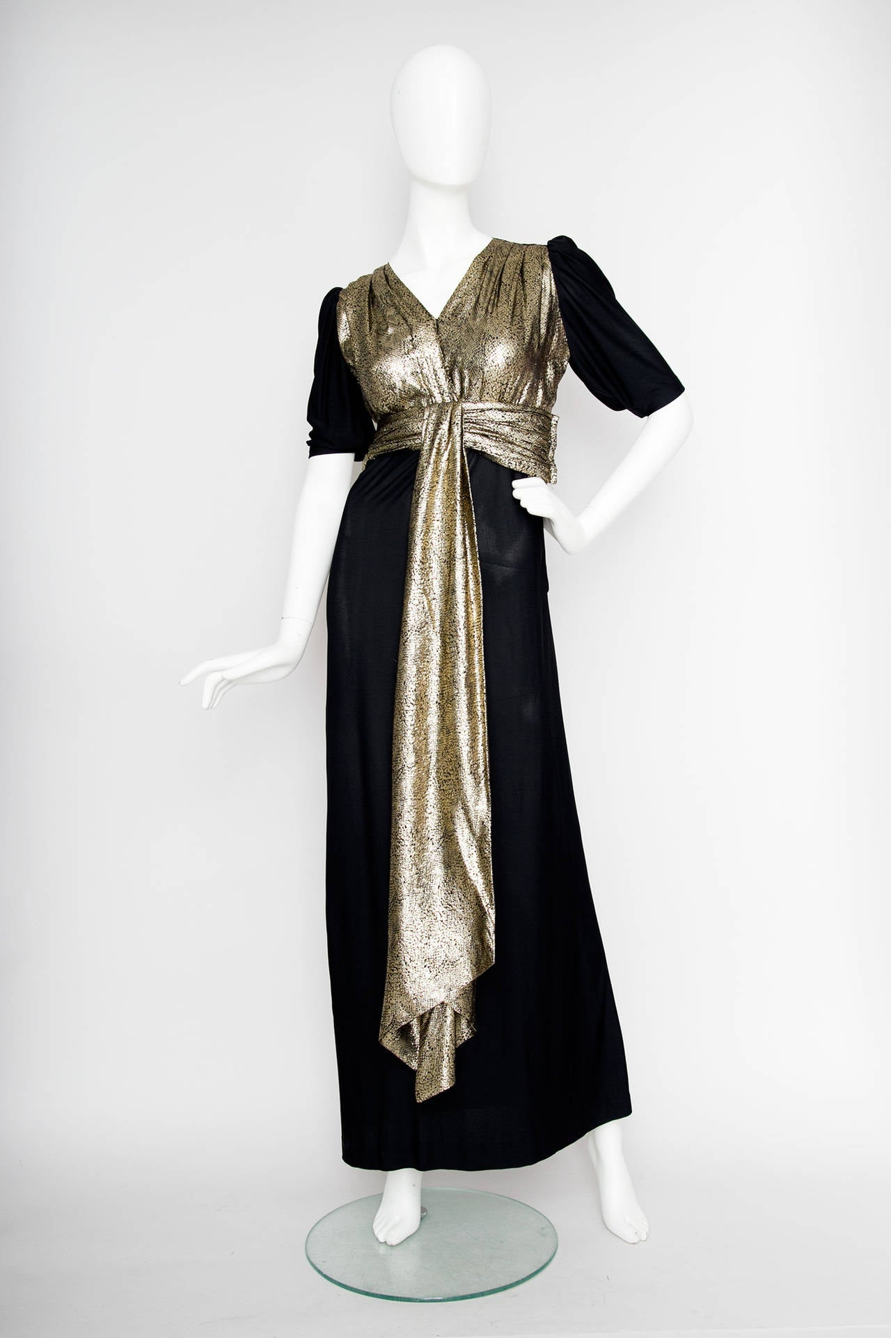 A 1970s silk jersey Yves Saint Laurent Rive Gauche black floor length evening dress with a gold-lamé top with a v-neckline, short sleeves and a detachable gold sash gently dropping down in the front of the dress.    The dress has a zipper closure