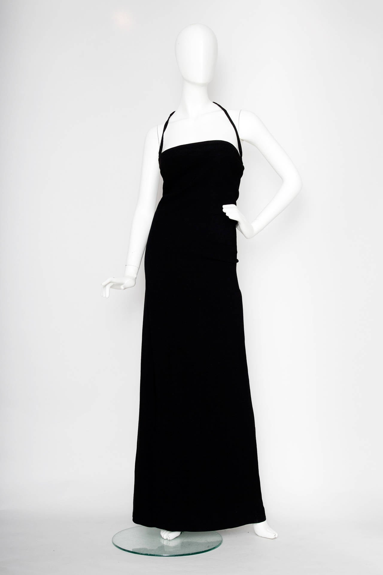 A stunning 1990s Jean Paul Gultier black minimalistic column dress that cuts straight across the bust, a halter neck strap and a back zipper and hook and eye closure.