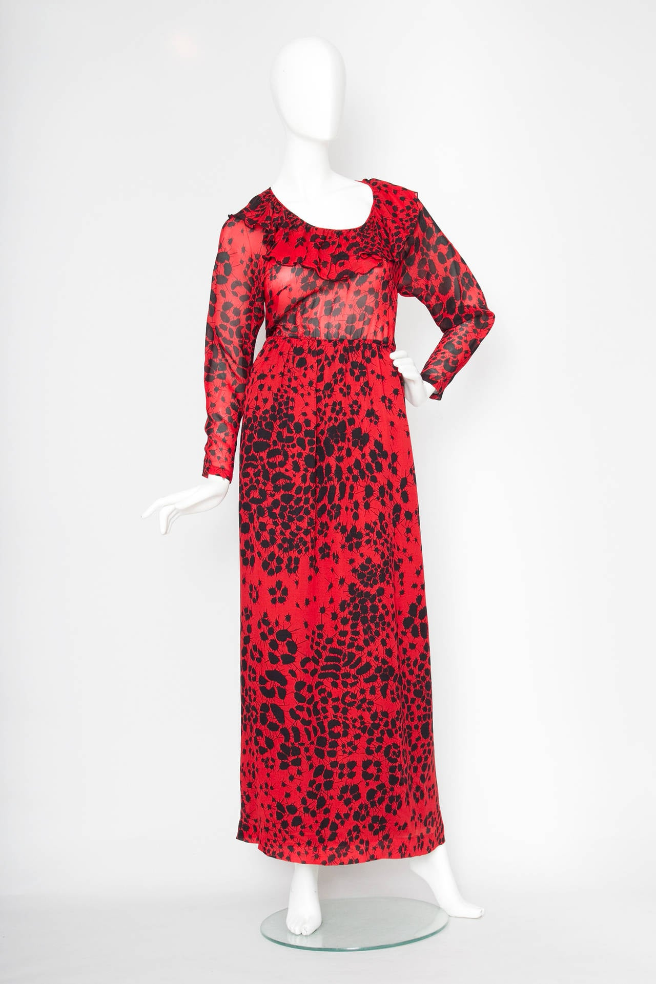 An absolutely gorgeous 1970s bright red Lanvin silk dress with an all over abstract black flower print and a nipped in waist. The dress has a sheer blousing top with tapered sleeves, a round neckline with delicate ruffle detail and a fully lined