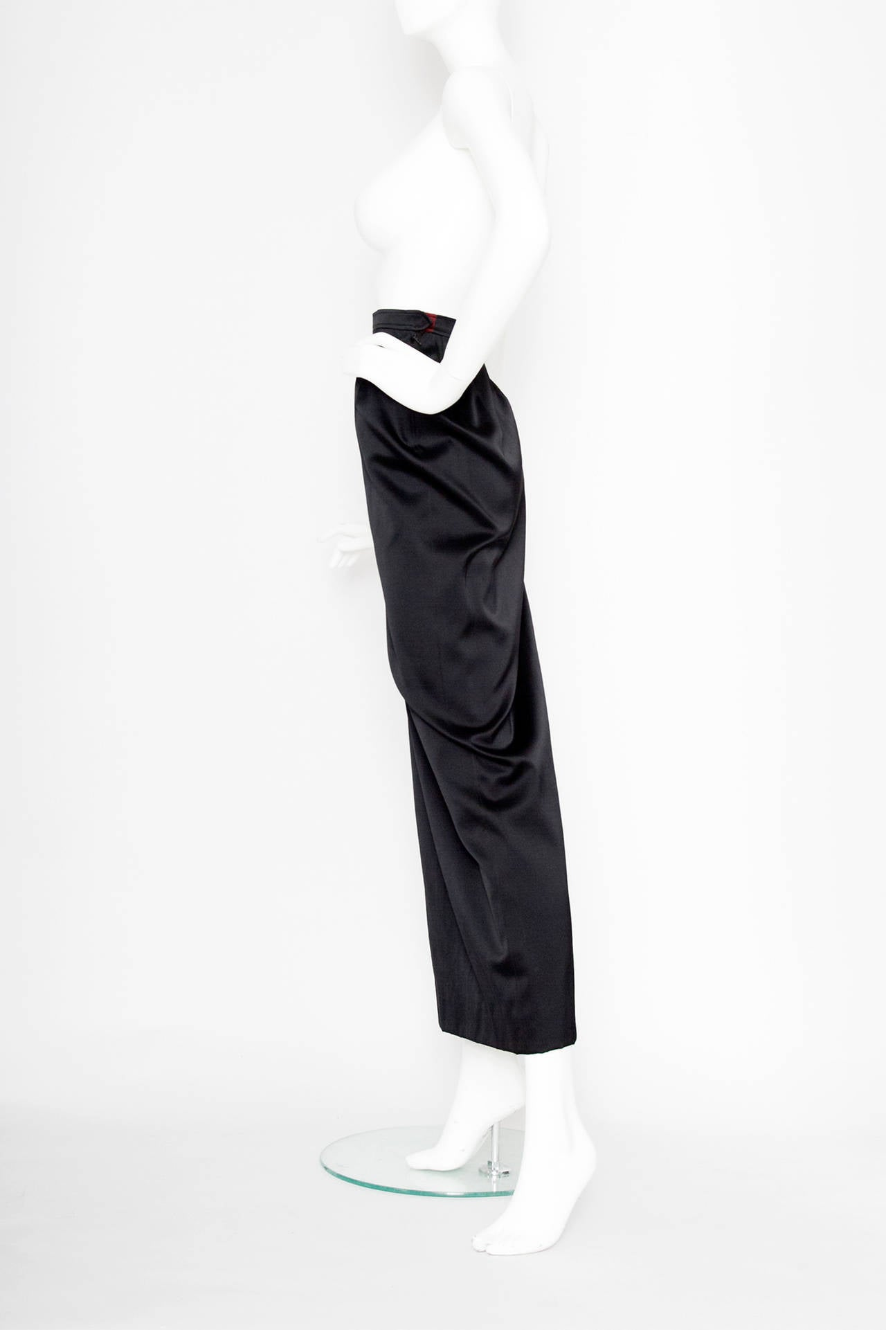 A sleek 1990s floor-length Yves Saint Laurent black silk satin skirt with a thigh high slit measuring 45 cm in the side. The skirt has a side zipper, a hook & eye and a single push button closure, concluded with a bordeaux insert in the trim.