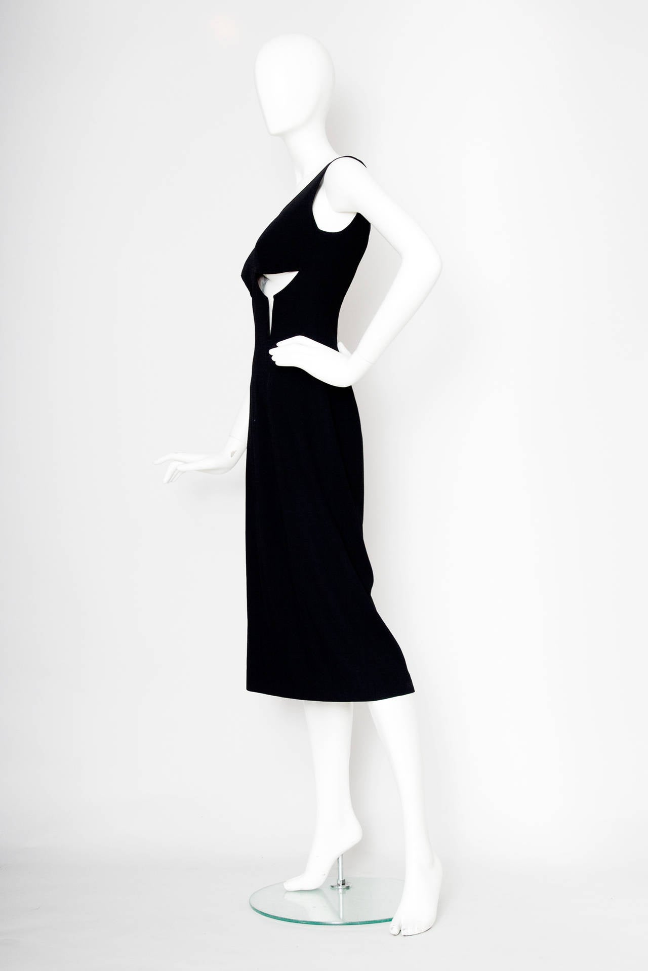 A daring 1990s Jean Paul Gaultier little black dress with cutout details below the bust. The dress cuts just below the knee and has a zipper closure in the back.  The dress is equivalent to that of a modern size Medium.