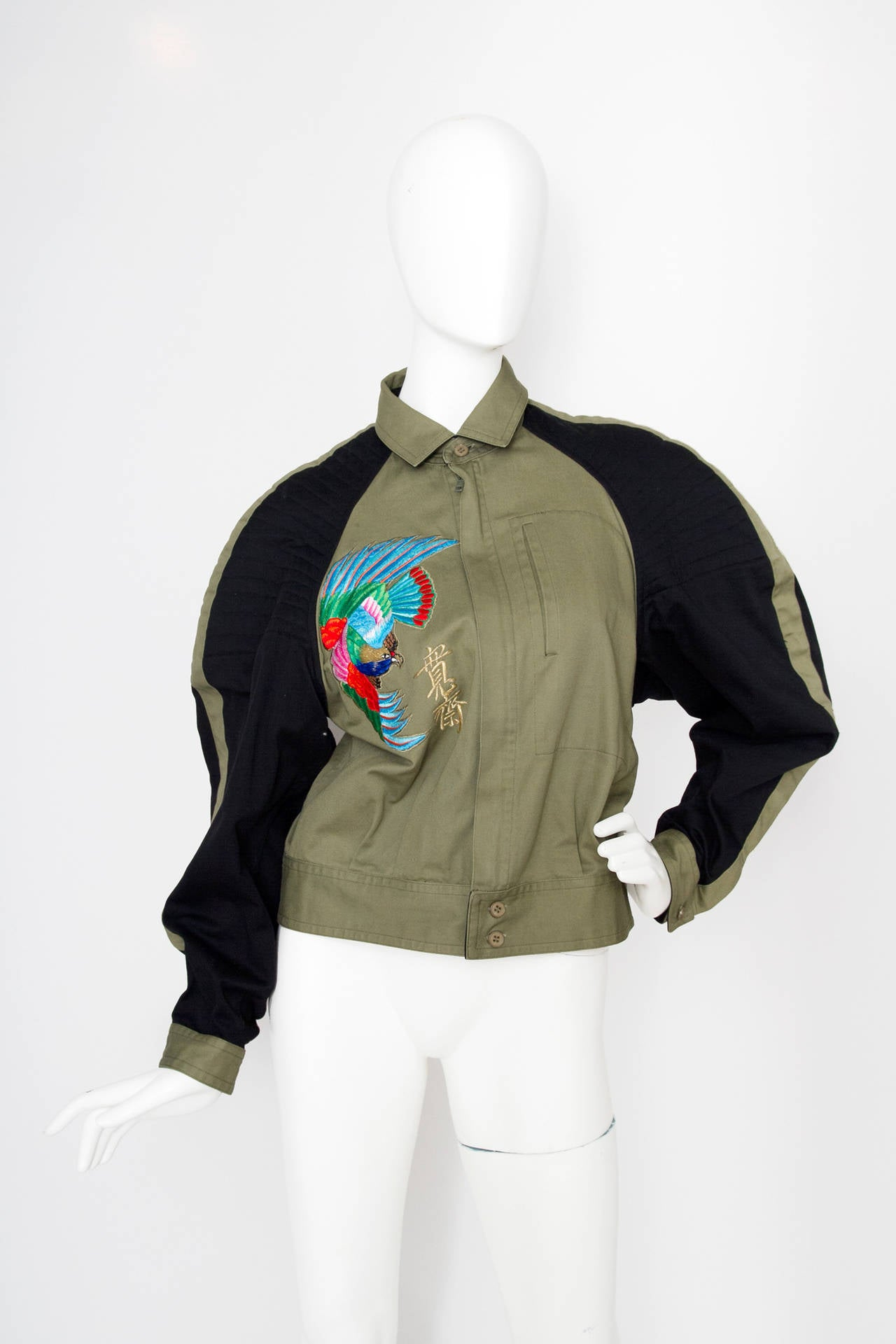 A 1980s Kansai Yamamoto cropped cotton bomber jacket with an extravagant embroidered bird pattern placed both on the front and on the back. The army green jacket has black panels on the sleeves and linear quit detailing on the shoulders. The jacket