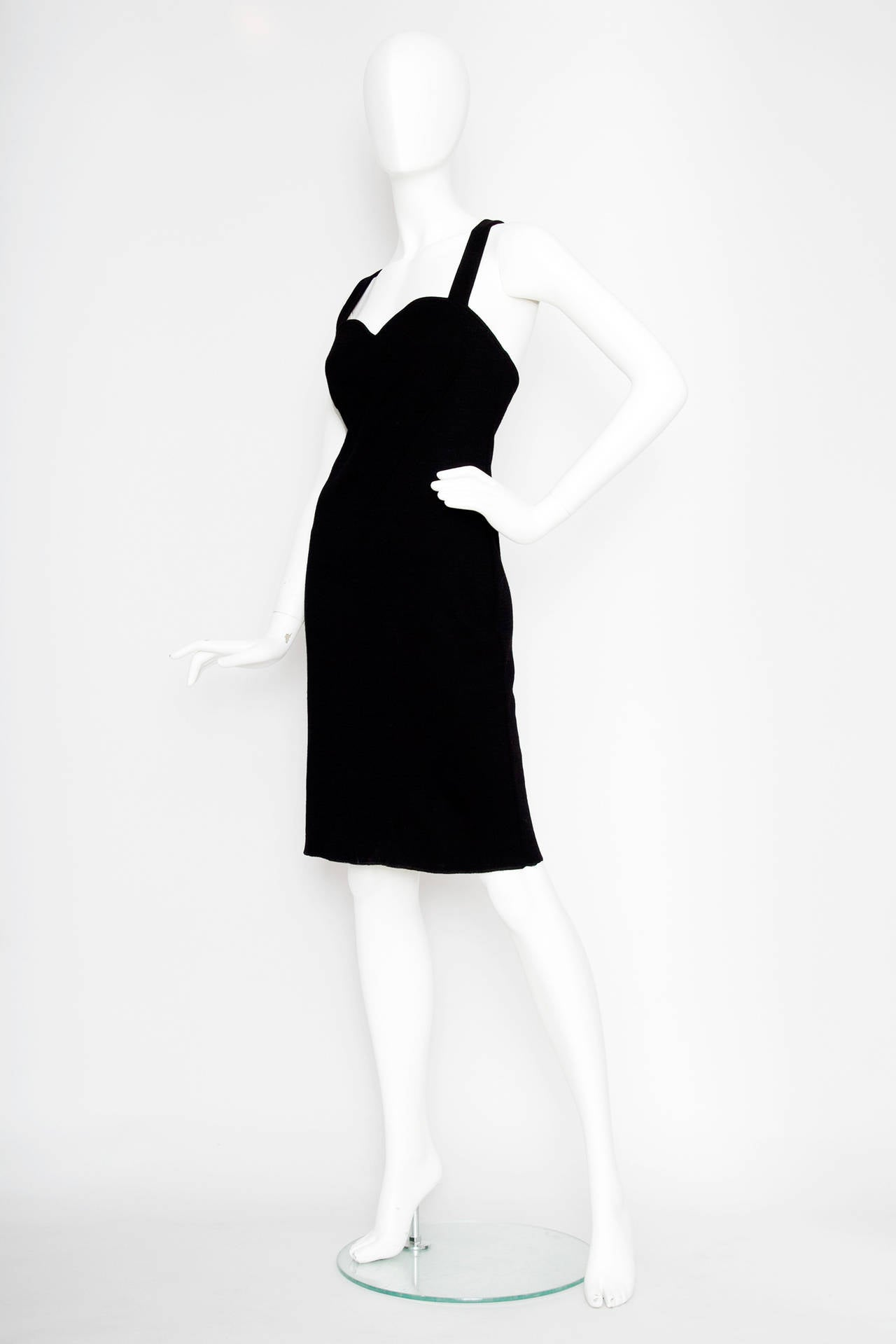 A gorgeous 1980s Yves Saint Laurent little black dress in cotton and woo fabric with some stretch to it. It has a sweetheart neckline and the straps cross over the back. The dress has a large heart detail on the front of the bust.   The dress