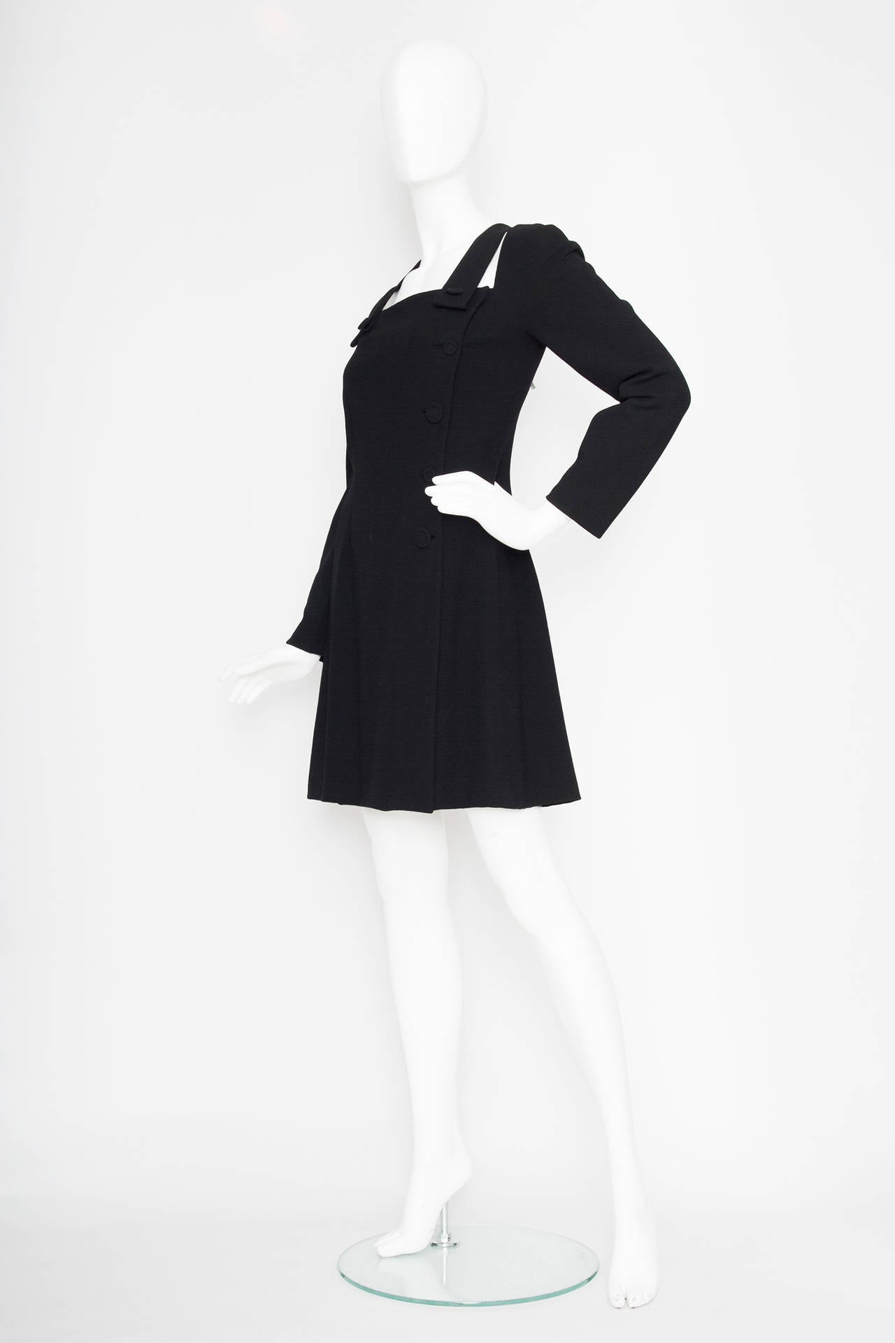 A 1980s little black Gianni Versace Couture wool dress with long tapered sleeves and a wrap detail on the front. Over the shoulders the dress has two suspender details that each are fastened with a button on the front of the square neckline. The