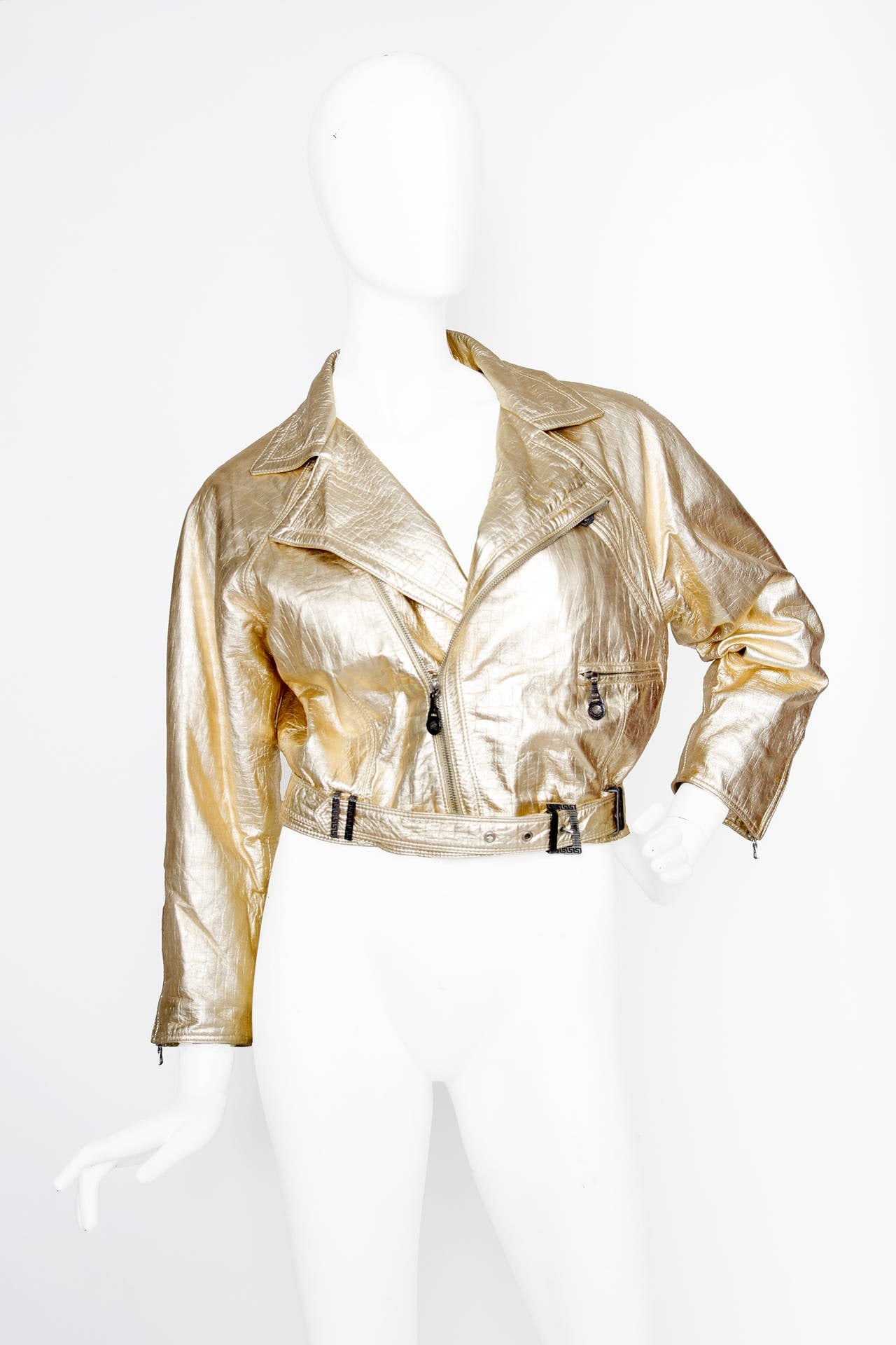 A 1980s Gianni Versace gold leather biker jacket with rounded shoulders and a cropped fit. The jacket has multiple pockets, zipper details on the cuffs (with medusa-head pulls) and comes with a matching waist belt with buckle closure. The jacket is
