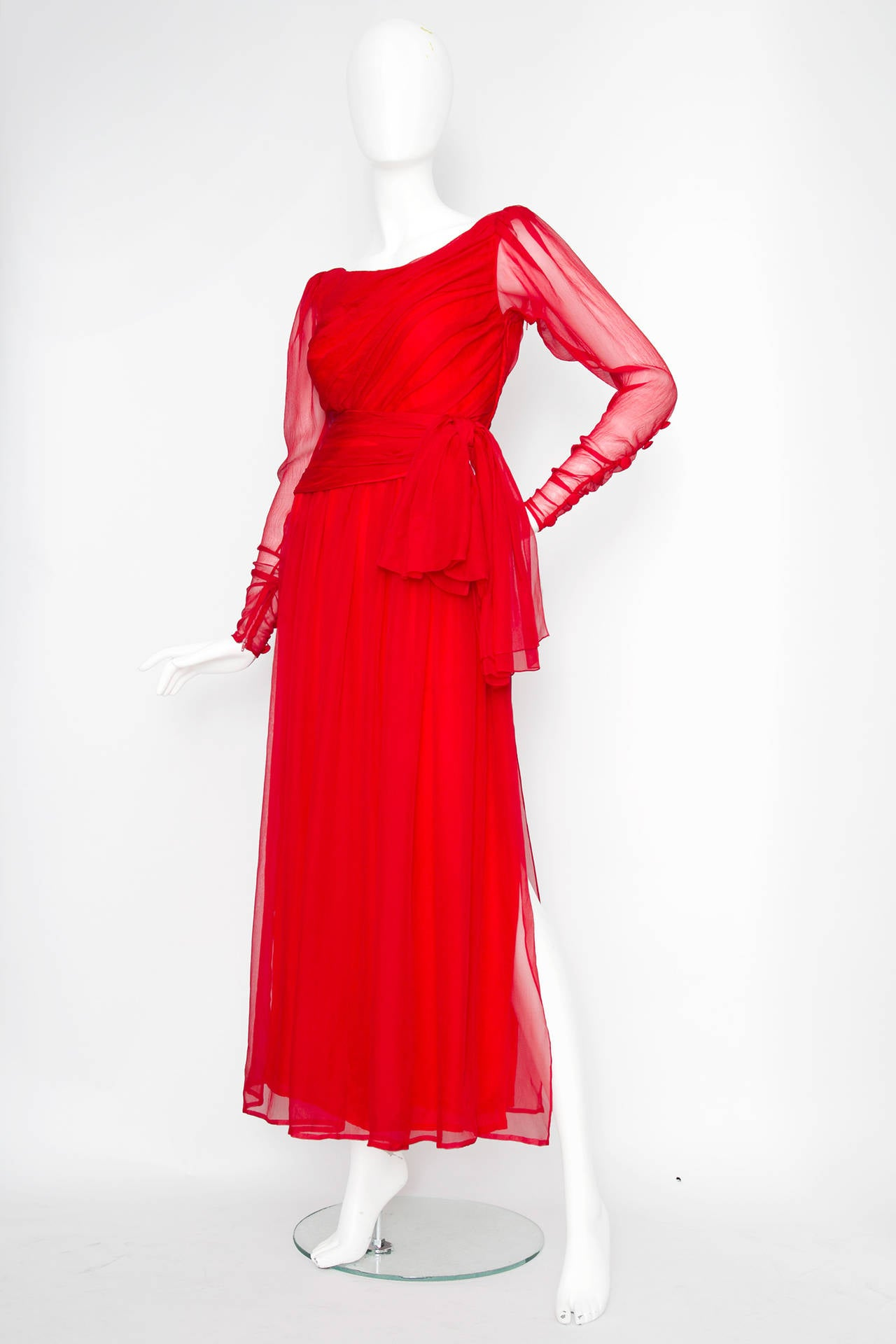 An absolutely stunning and very rare 1983 Yves Saint Laurent haute couture gown in bright red silk chiffon. The gown has a scoop neckline and long sheer sleeves with button details and a zipper closure on the cuffs. The gown is fully lined and has a