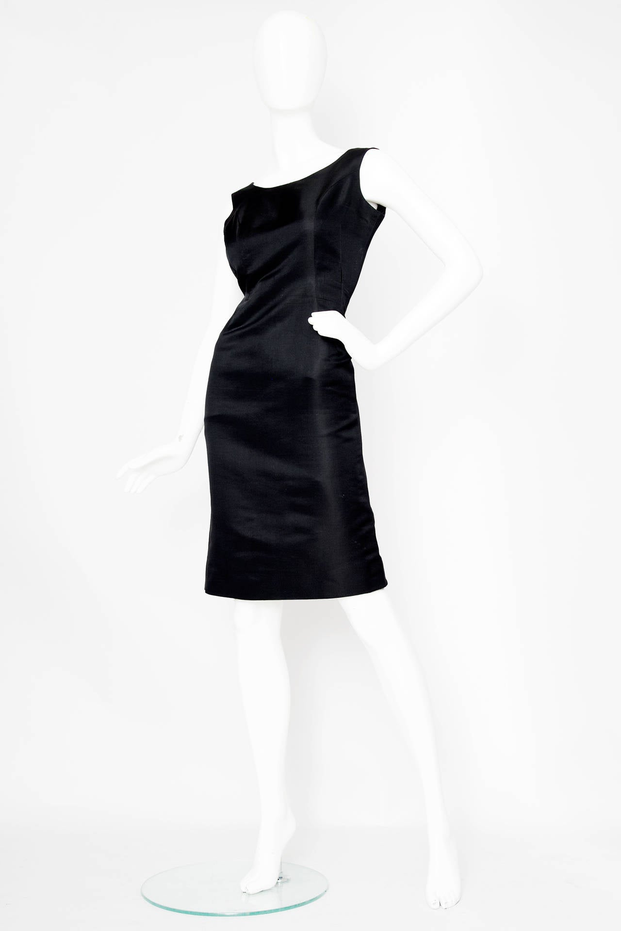 A stunning 1960s Pierre Cardin Haute Couture dress in a heavy black silk with impeccable couture finish. The classic shift dress has paneling down the front and a simple scoop neckline. The dress has a low-cut back and closes with a zipper and hook