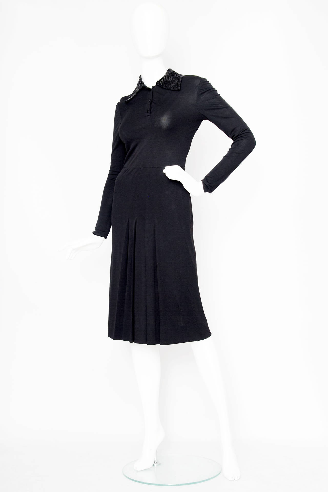 A stunning 1960s Miss Dior silk jersey dress with tapered sleeves and a nipped in waist. The dress has gentle pleats on the knee length skirt and a button down closure on the front of the blouse. The collar is beaded in a stripped pattern with both
