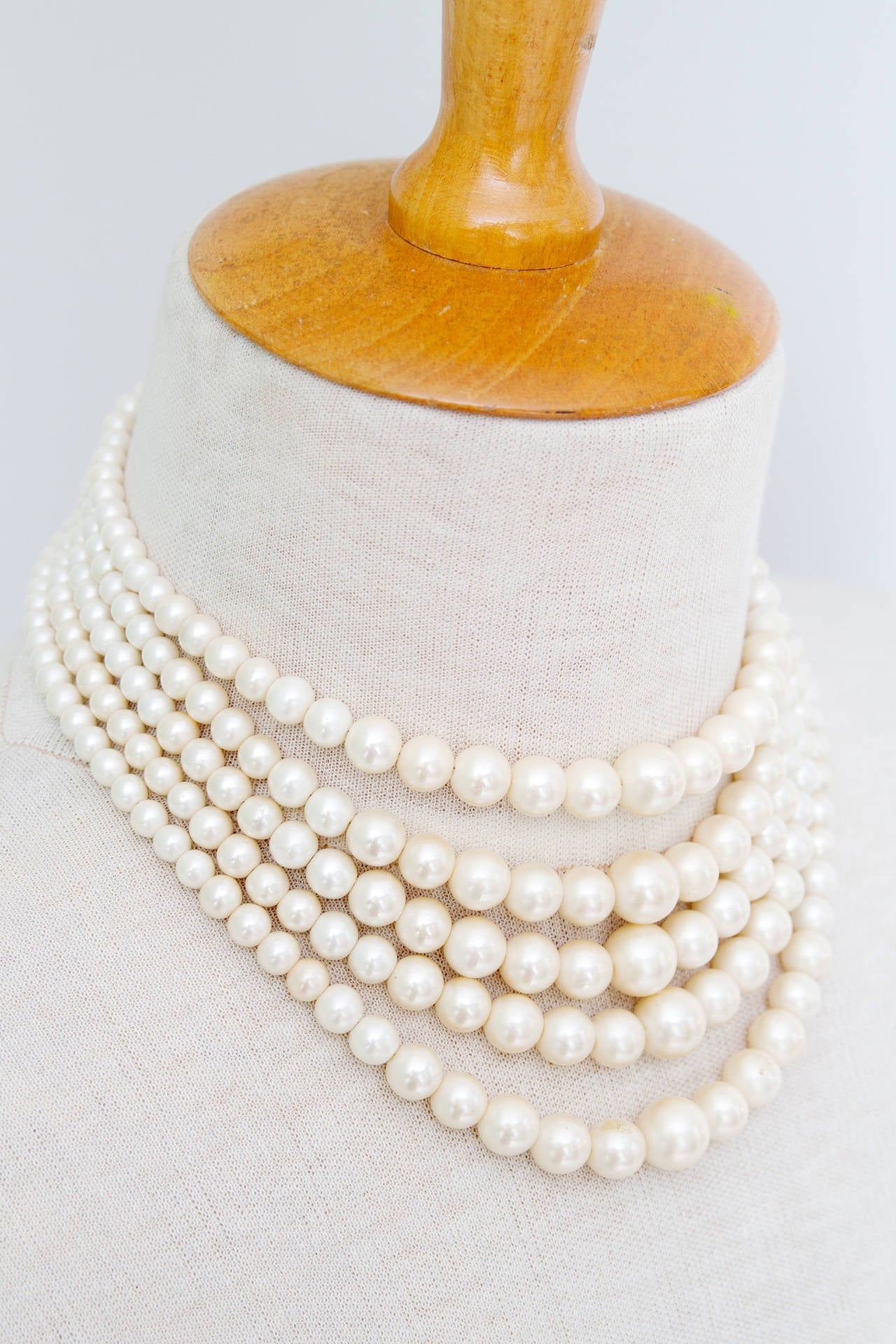 A 1960s Christian Dior five strand pearl chocker with silver hardware. The size of the pearls range from 0.5 cm to 1.2 cm in diameter.  The necklace is stamped: Christian Dior 1961.