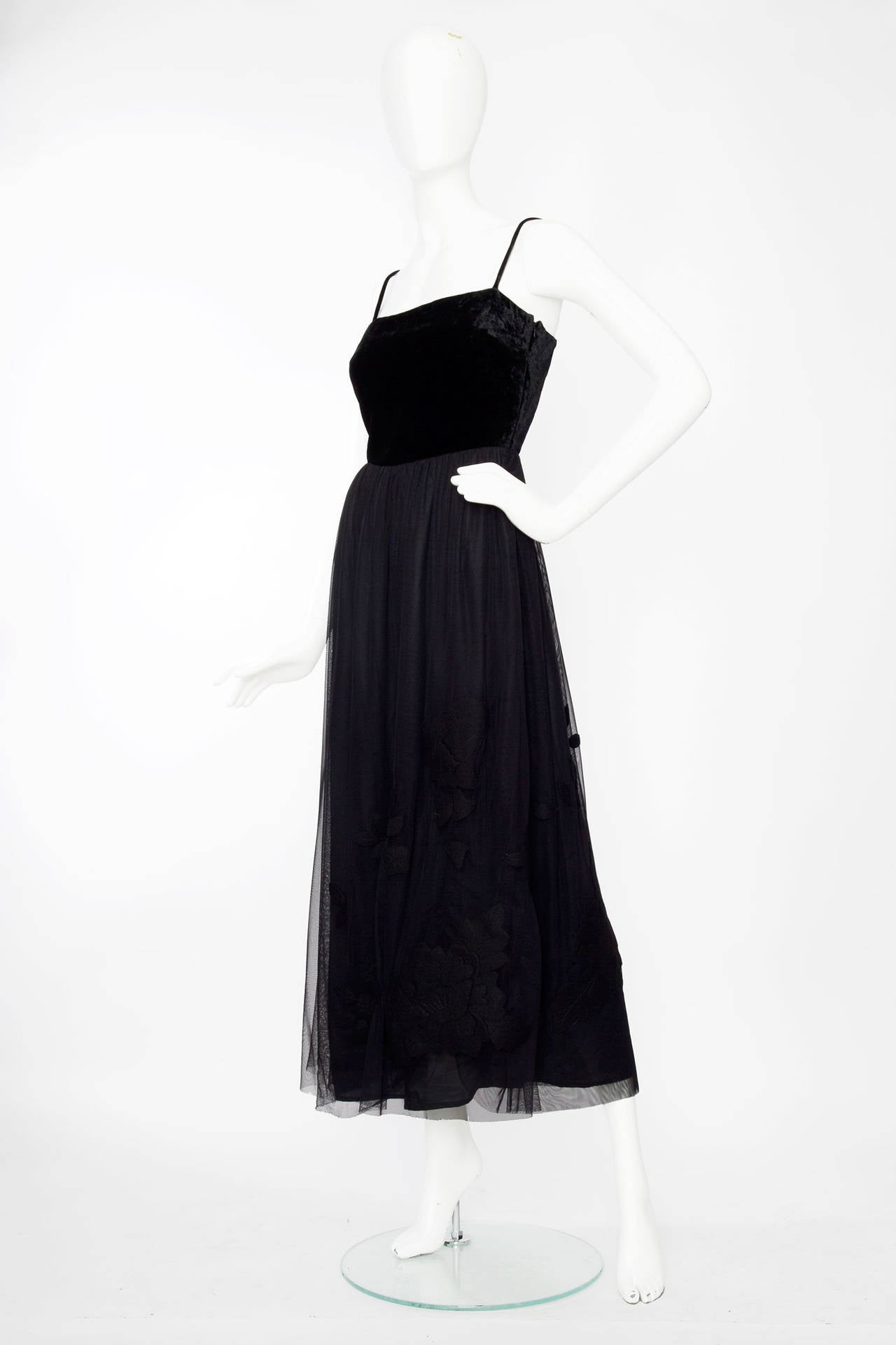 A late 1980s early 1990s Moschino Cheap & Chic ball gown with a silk velvet top and tulle skirt with felt flower applique. The skirt cuts just above the ankle and is fully lined. The dress has a side zipper closure. 