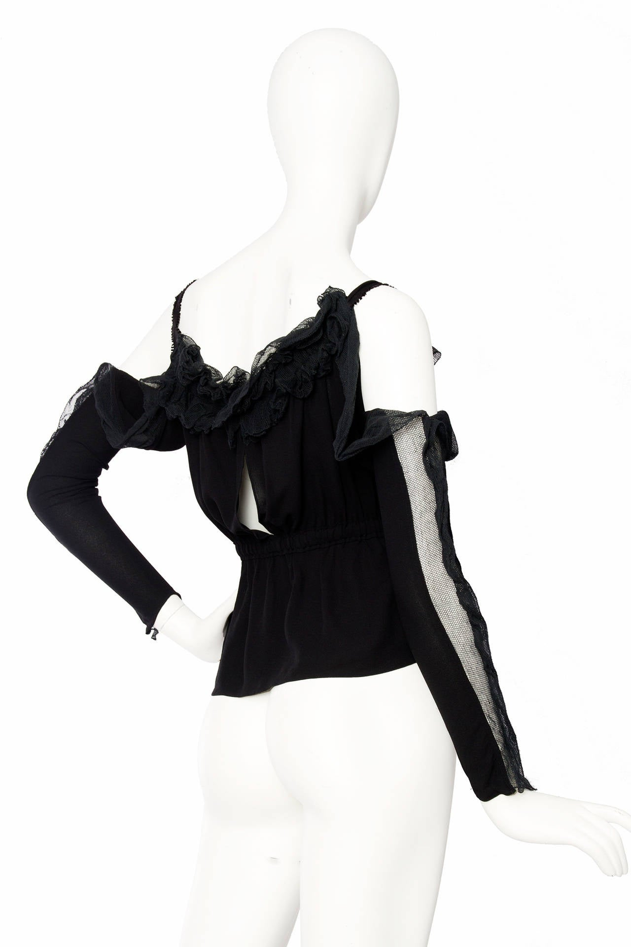 A 1990s Black Yves Saint Laurent silk blouse with lace trim and a split down front and back. The blouse has an elasticated waistline and off the shoulder sleeves that are attached under the arm. A single ribbon detail to each shoulder frames a