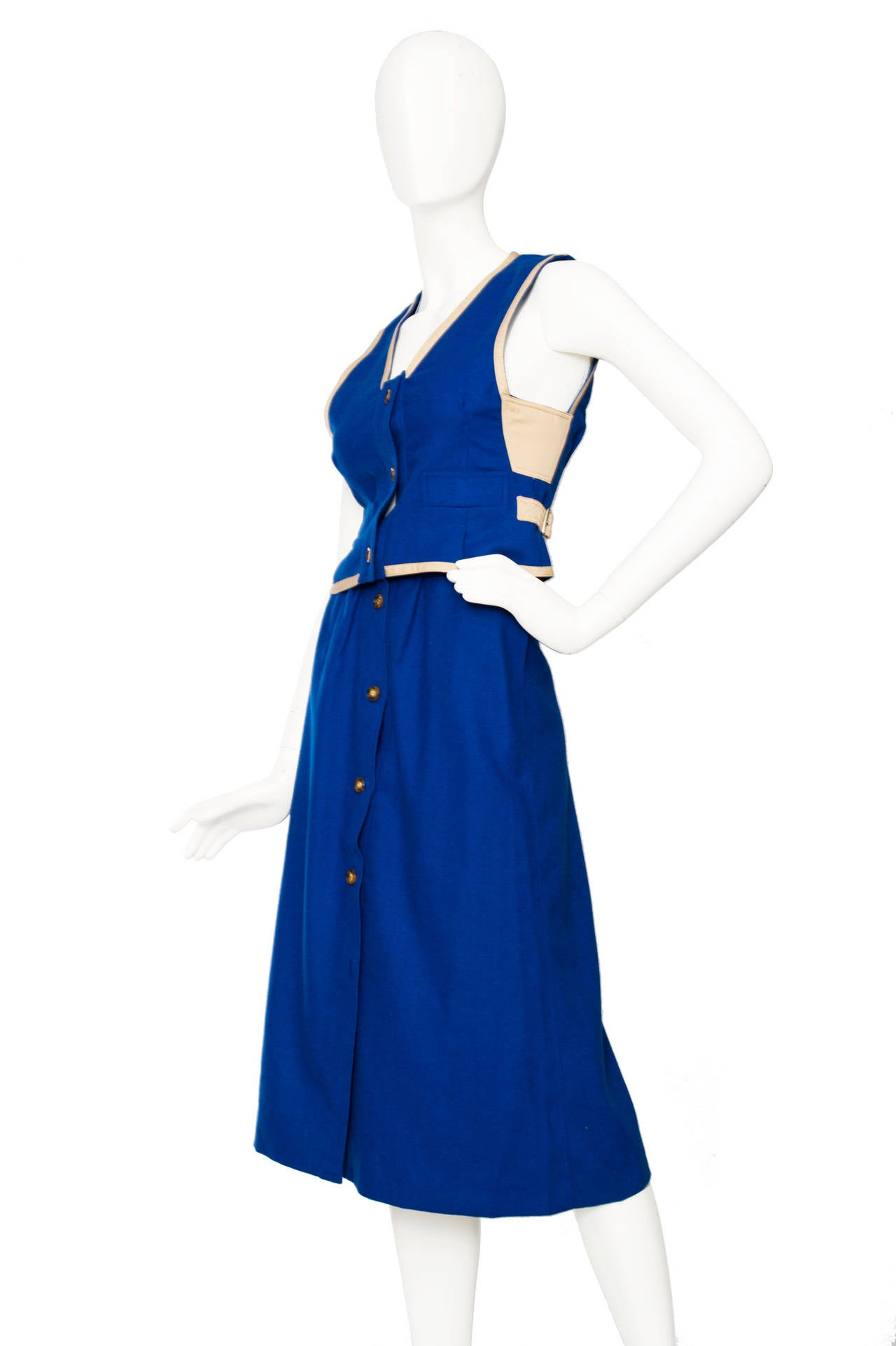 A 1960s Courrèges electric blue a-line wool skirt and vest ensemble. The top have a delicate off-white leather trimming all round, dart inserts under the arms and a leather buckle detail is framing the waistline. Both the top and bottom have an