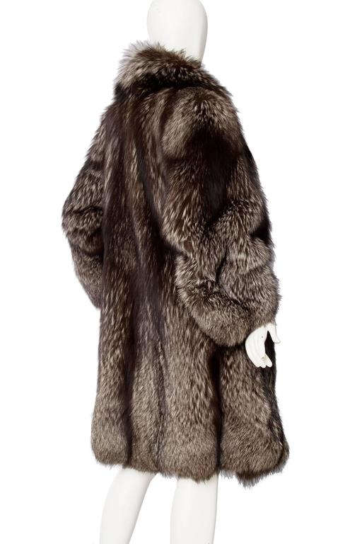 A glamorous 1980s silver fox fur coat with extravagant shoulders and voluminous sleeves. The coat has side pockets and beautiful detailed paneling running down the back.  
