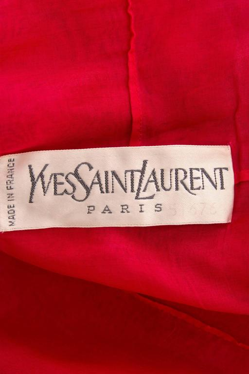 A stunning 1980s Yves Saint Laurent bright red haute couture evening gown with a gorgeous hand made detailed corded lace overlay.   The dress has a plunging neckline with the lace scalloping over and 3 quarter length transparent sleeves and puffed