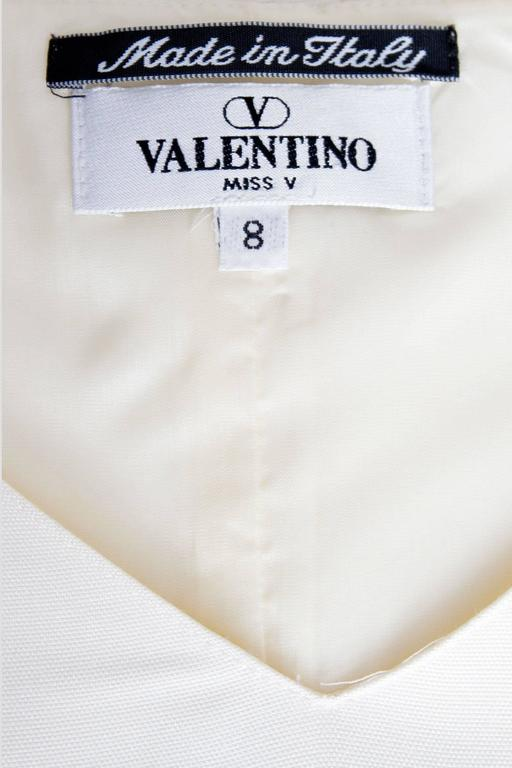 A lovely 1980s Valentino Miss V off-white silk dress with cap sleeves and a demure v neck in the front. A simple skirt cuts just below the knee and a drop waist with a beaded belt detail gives the dress an ekstra feminine touch. The cylinder shaped