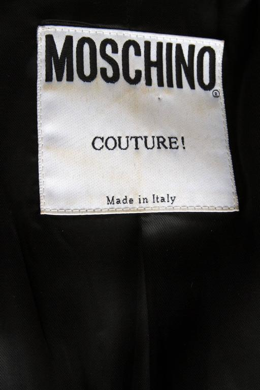 A 1990s black Moschino Couture blazer with a deep round cut front exposing an attached black lace undergarment. The bustier has an oval shape and close in the front with a gold buckle and a silky ribbon that can be tied in front. A flap pocket is