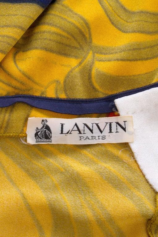 A 1970s Lanvin graphic dress with a fitted bodice and a-line skirt. The dress has a high neckline, long tapered 3/4 length sleeves and a back zipper closure. The stunning print is held in striking bold colors of yellow, orange and navy. The skirt