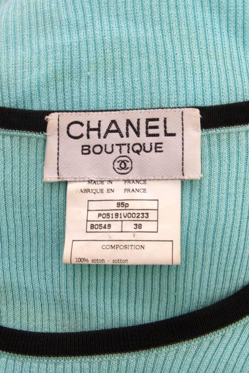 A cute 1990s turquoise Chanel cropped cotton top with cap sleeves and contrasting black piping along the hem, neckline and sleeves. In the centre front, the top has a small black Chanel logo embroidered. 