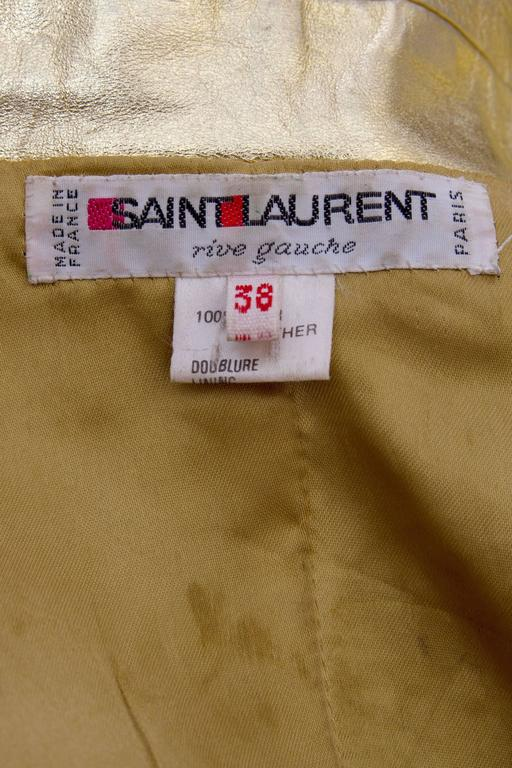 A 1990s high voltage glamour Yves Saint Laurent double breasted gold leather jacket with exaggerated shoulders and wide lapels. Four large rounded gold buttons ads definition to the waistline and two large patch pockets on each side of the hip gives