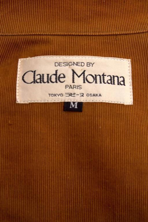 A light kaki colored 1980s Claude Montana cotton trench coat with exaggerated shoulders and a stand up color with two brass push buttons for closure. The coat has a buckle deal around the cuff  and contrasting light brown piping across the