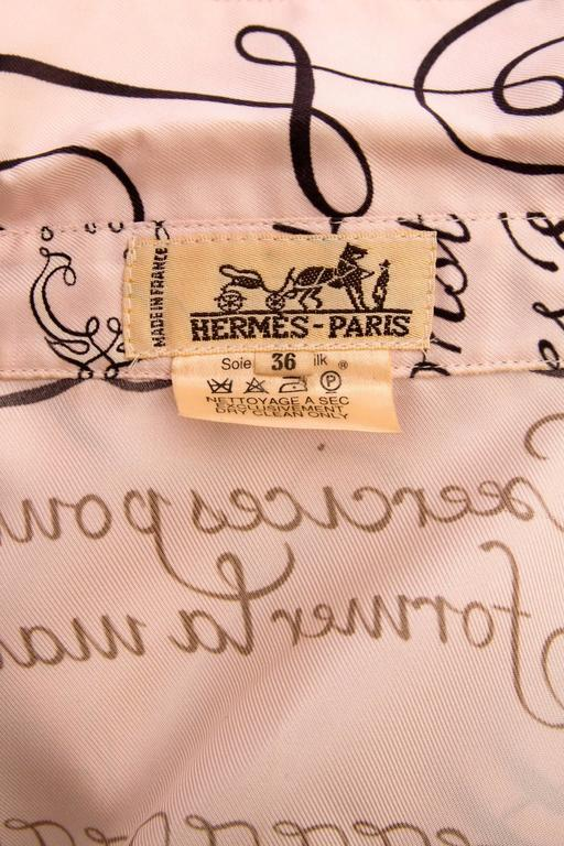 A 1980s light pink Hermés tailored silk blouse with 'l'Art d'Ecrire' print in black, white and browns. The blouse has long sleeves with one buttoned cuffs and a front buttoned closure. All plastic buttons are engraved with *Hermes, Paris'.