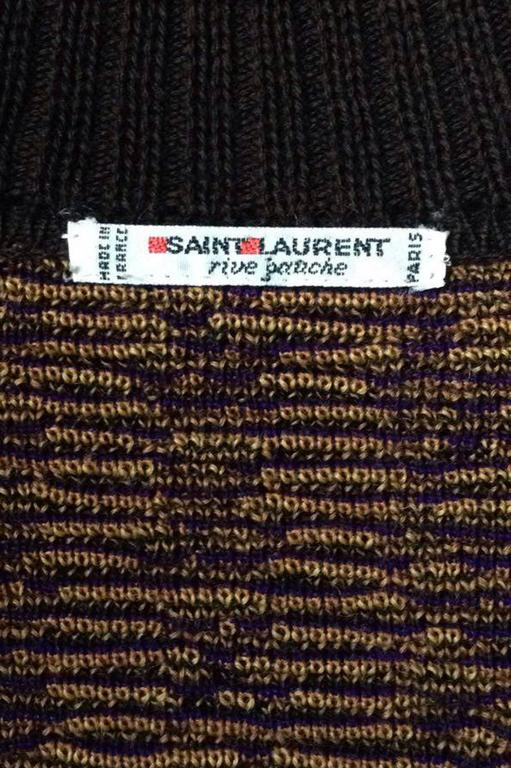 A colorful 1980s Yves Saint Laurent double breasted wool cardigan with a large abstract print in demure brown, purple and yellow colors. The double breasted closure is completed by eight sculptural gold buttons. 