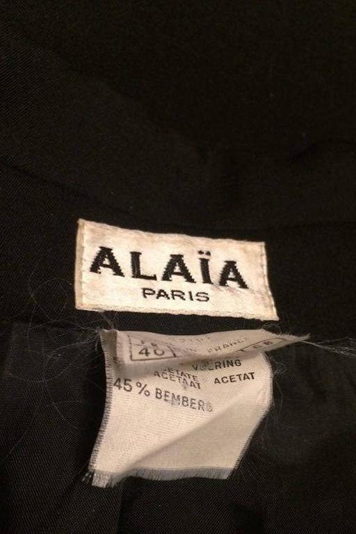 A classic 1990s black cropped Alaïa blazer with a deep v-neckline, slim lapels and a double buttoned closure. Structured shoulders are held in place with small shoulder-pads and one buttoned cuffs ads deal to the excess length sleeves. The blazer