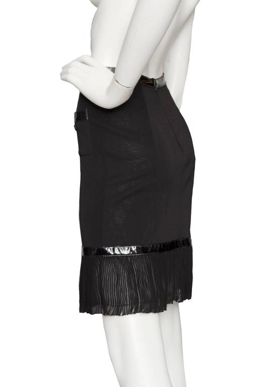 A little black 1990s Chanel viscose mini-skirt with vinyl detail at the hem- & waistline. The fitted skirt has a sheer overlay and a flared trim at the hemline. Small patch pockets are situated at the hip and also feature a vinyl trim at the