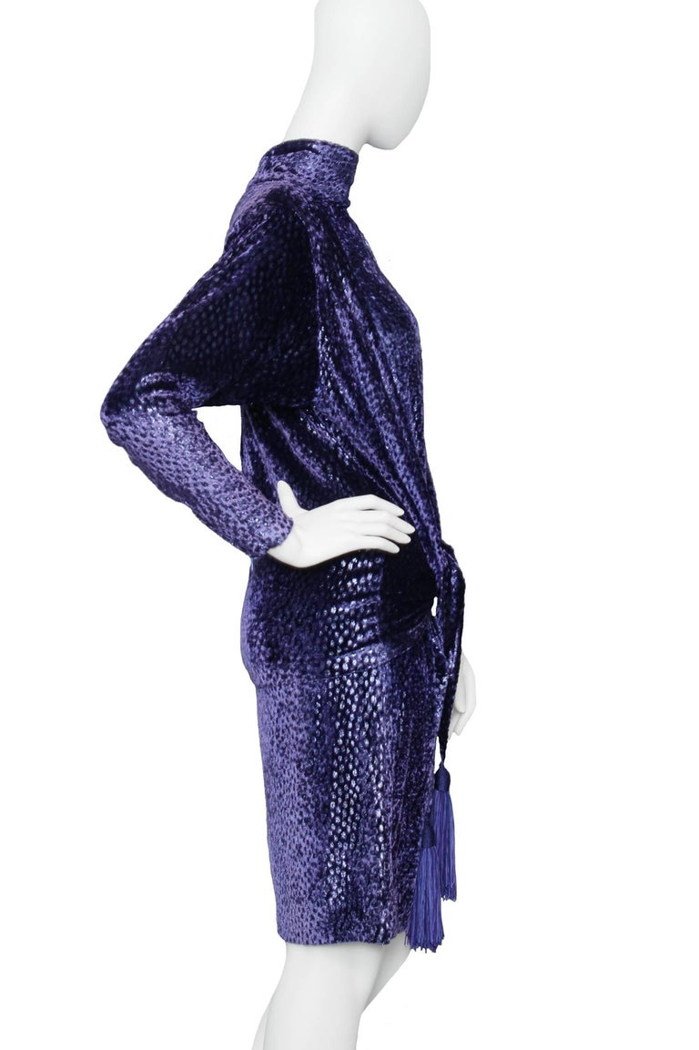 A great 1980s Christian Dior dark blue velvet cocktail dress. The dress has long tapered sleeves with a zipper detail at the cuff, large shoulder-pads for extra glamour, a round neckline and a layered hemline.    The size of the dress corresponds to
