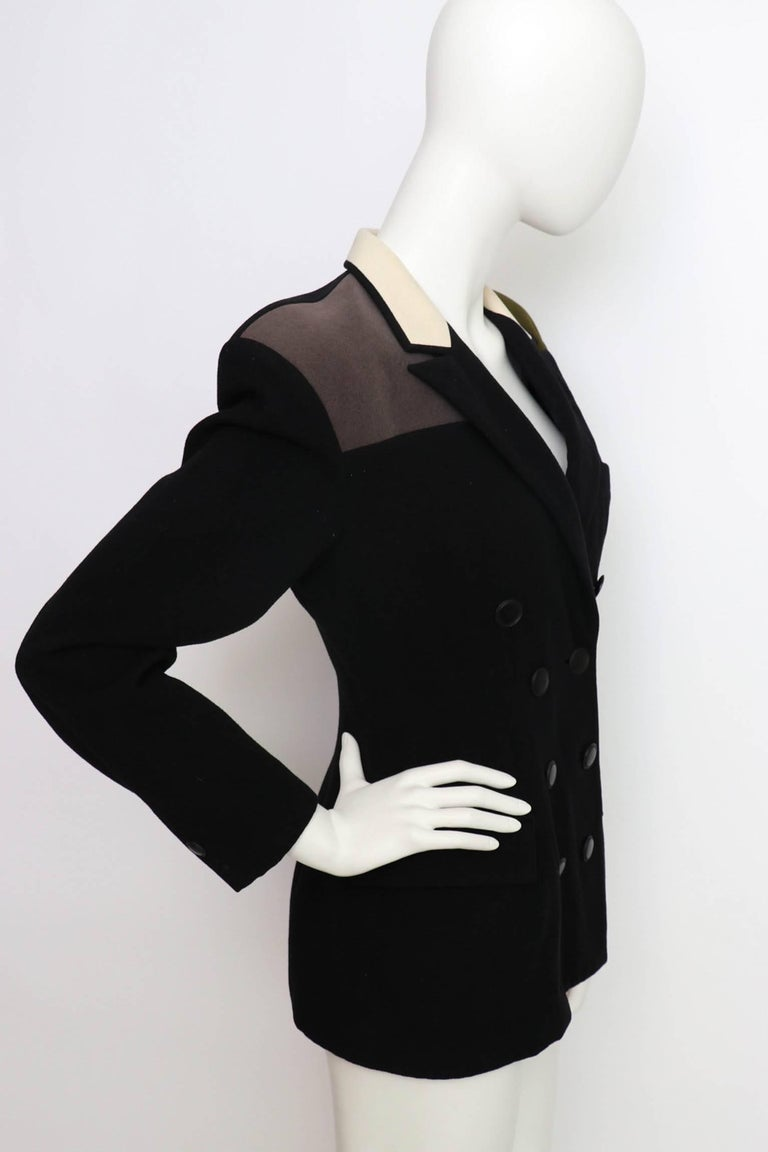 A gorgeous double-breasted 1980s Yohji Yamamoto black fitted wool blazer with long sleeves, a fitted waist and contrasting panels at the shoulder and collar. Both a dark forest green and charcoal colored panel are situated on each shoulder whilst an