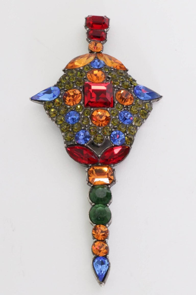 An absolutely stunning 1970s Yves Saint Laurent multi-colured rhinestone studded brooch. The stone settings are held in bold primary colours set on a base of minor sparkling green studs as well as vary in size and shape.   Stamped: