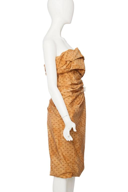 A sculptural handmade Bottega Veneta draped bandeau dress in burnt orange with a brown print. The dress is made in 100% cotton and has a built-in corset to maintain the shape of the bust area. In the left side, the dress has zipper closure and a