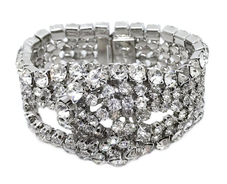 Circa 1960s William deLillo wide, rhodium plated silver tone metal cocktail bracelet with an intertwined loop design.  It is prong set with large clear faceted glass stones. This large statement bracelet is from the designers collection.  The