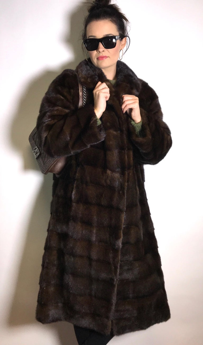 High class dark brown mink coat with crosswise cut. Exclusively made by the furrier.  Size: 40 - 42 / M - L Total length: 117 cm Shoulder width: 44 cm Sleeve length: 50 cm  The coat is in excellent condition, almost never worn.  - Our model wears an