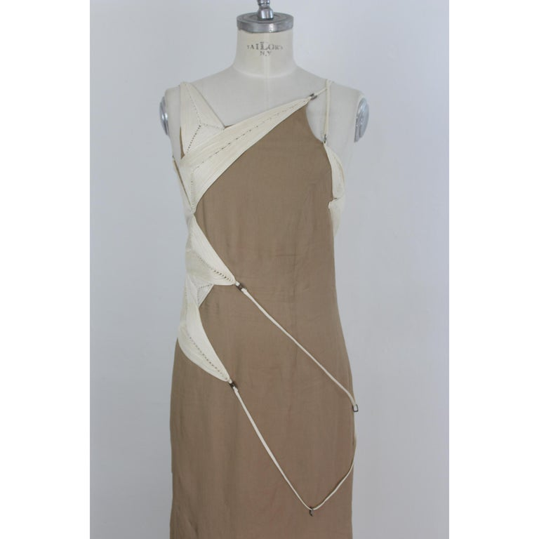 Long evening dress designed by the Italian fashion designer Angelo Mozzillo. It is 100% silk, beige. It is characterized by a corset sewn in relief. It behind the shoulder has a beautiful weave of customizable laces. Unique in its kind. Excellent
