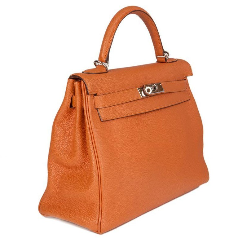 Hermes 'Kelly II 32 Retourner' bag in orange Veau Togo leather with gold-plated hardware. The interior is lined in Chevre (goat skin) with a divided open pocket against the front and a zipper pocket against the back. Has been carried and is in