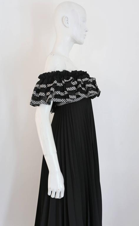 A beautiful Jean Varon pleated evening gown, circa 1970s. The gown features elasticated bust and arm holes, tiered ruffled bust with checkered trim and full pleated maxi skirt.   Bust 32 inches