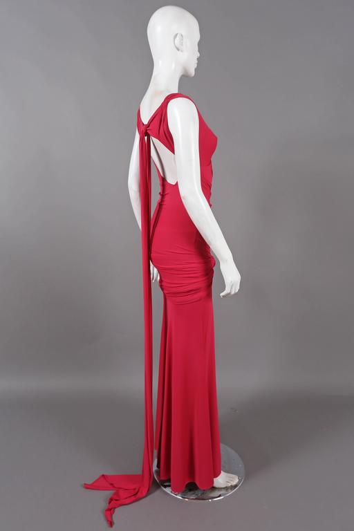Magenta evening gown by DONNA KARAN, the dress feature 1930's inspired drapery and knotting, open back and long sash train. The dress can be styled in various ways.