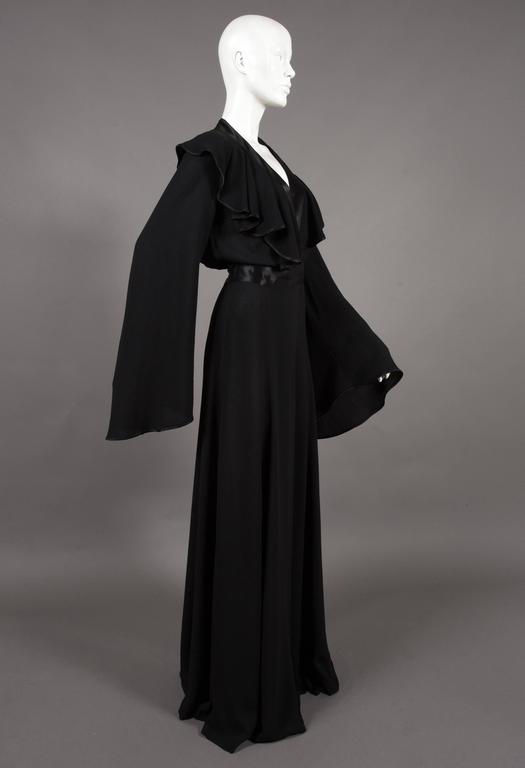 Rare Ossie Clark black moss crêpe wrap around evening dress, circa 1970, printed with the Ossie Clark couture label, size '12', with stain top stitched lapels and satin sash, full bell sleeves and leg slit.   Size:  Shoulder to shoulder -