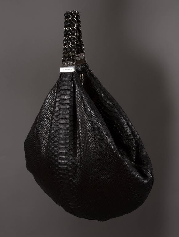 Limited edition Chanel hobo bag designed by Karl Lagerfeld, spring-summer 2007 runway collection. Black king python skin, silver hardware, 'CC' logo keychain, zip closure, satin lining, and three strand chain shoulder strap. The bag was first shown