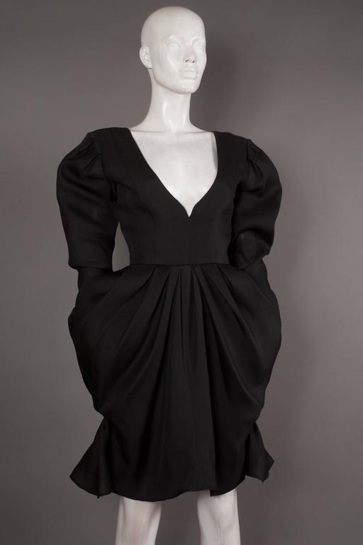 A Yves Saint Laurent tulip evening dress, circa 1993. Black silk organza, deep v-neck, puff sleeves, draped tulip skirt, front hidden pockets and zip closure at rear.