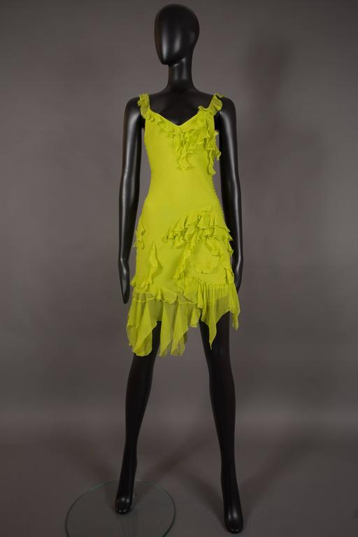 A Christian Dior silk chiffon mini dress, circa 1990s. Designed by John Galliano, spaghetti straps, multiple fabric button closures on side seam and asymmetric chiffon ruffles throughout.